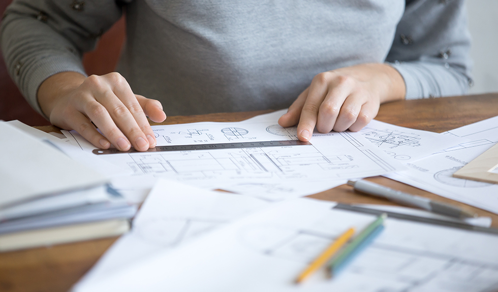Female hands, working at the desk with a ruler and a drawing. Education concept photo, close-up